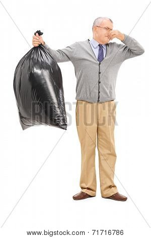 Full length portrait of a senior holding a stinky garbage bag isolated on white background