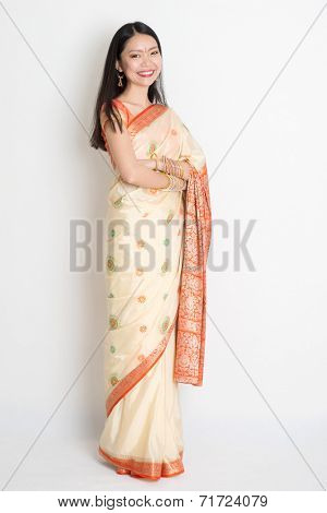 Full length confident fair skin tone Asian Indian female smiling and standing on plain background.