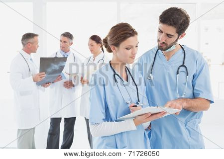 Nurses reading a file together with doctors behind them