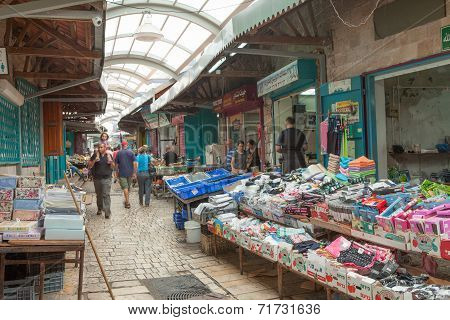Tourists and shoppers walking by Acre grand bazaar