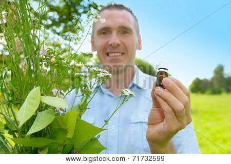 Man homeopath herbalist picking up wild herbs with a bottle in hand