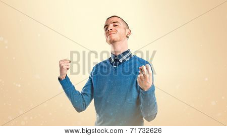 Young Man Winner Over Isolated Ocher Background