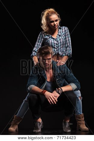 Hot couple posing for the camera, woman behind her boyfriend, resting her hands on his shoulders