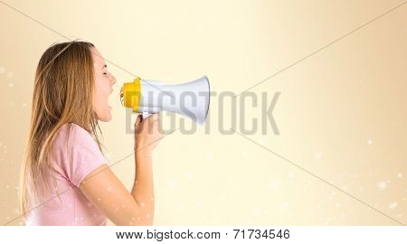 Blonde Girl Shouting With A Megaphone Over Ocher Background