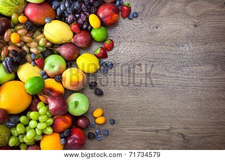Different Organic Fruits  with  water drops on wooden table background - Healthy Eating