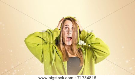Young Girl Doing Surprise Gesture Over Ocher Background