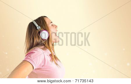 Young Blonde Girl Listening Music Over Ocher Background