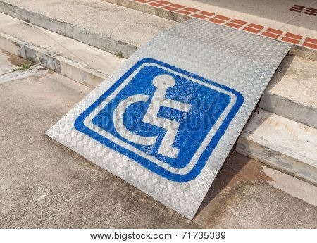 Ramped Access, Using Wheelchair Ramp With Information Sign On Floor.