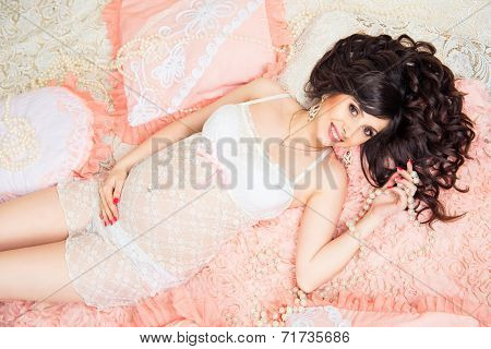 Smiling Beautiful Pregnant Brunette Girl In Soft Peach Pillows