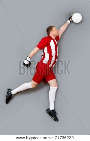 Goalkeeper catching the ball over grey background