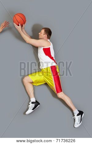 Muscular basketball player passing the ball over grey background