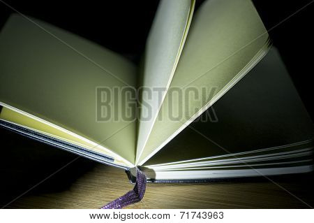 open book with incident light from the side on desk