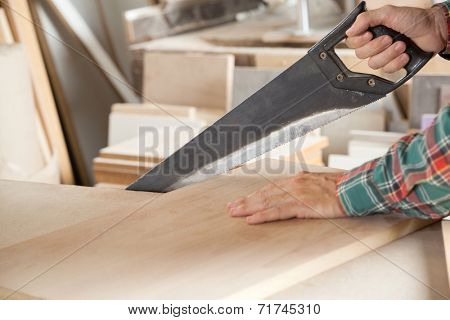 Cropped image of carpenter cutting wooden plank with handsaw at workshop