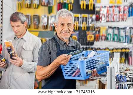 Portrait of smiling senior salesman holding tools basket with customer in background at hardware store