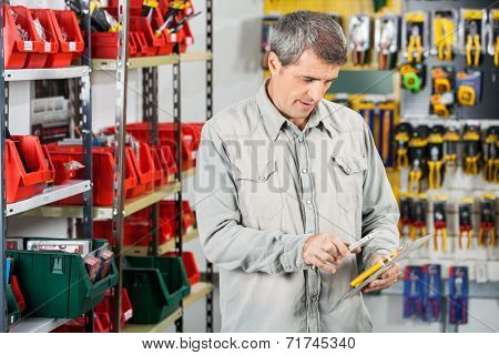 Mature male customer scanning tool packet through smartphone in hardware store