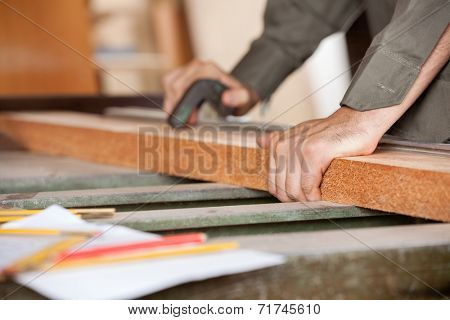 Cropped image of carpenter cutting wood with tablesaw in workshop