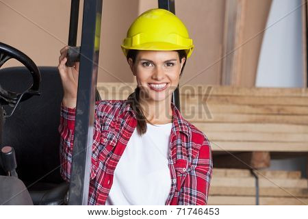 Portrait of confident female architect in hardhat by forktruck in workshop