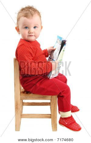 Baby girl dressed in red sitting on chair reading a magazine looking at camera isolated on white