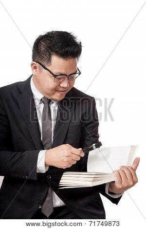Asian Businessman Reading A Book Through Magnifying Glass