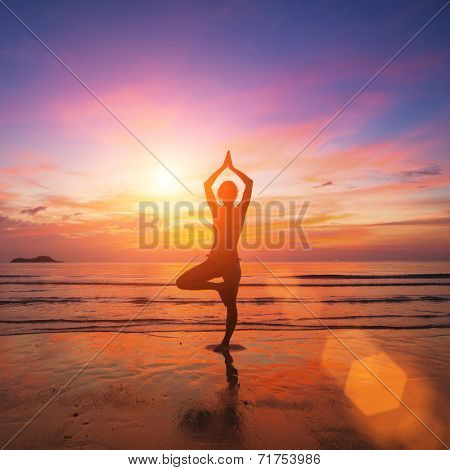 Silhouette of a young woman practicing yoga in the rays of the surrealist sunset at the seaside.