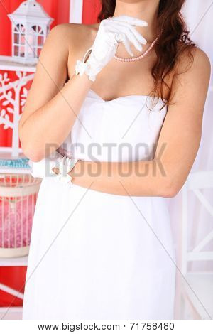 Beautiful bride in wedding  dress and gloves, close-up, on  home interior background