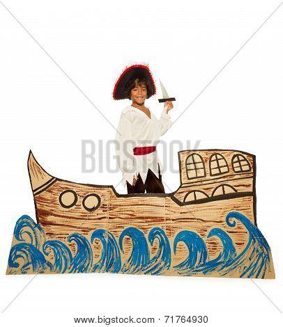 Black boy in costume of pirate on cardboard ship