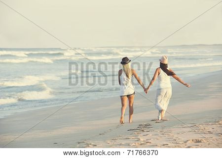 Young attractive lesbian couple walking along beach