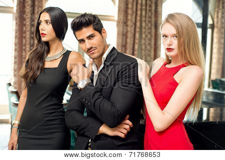 Portrait of a handsome fashionable man with two charming women posing
