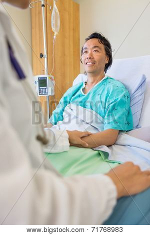 Mature male patient being consoled by doctor on bed in hospital
