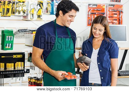 Worker accepting payment through smartphone from woman in hardware store