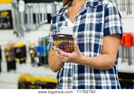 Midsection of female customer scanning product's barcode through mobilephone in hardware store