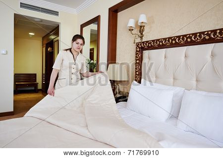 Hotel service. female housekeeping worker maid making bed with bedclothes at inn room