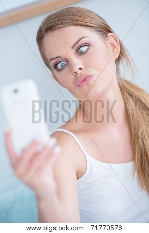 Young woman pulling a face as she poses for a selfie on her mobile phone squinting at the screen