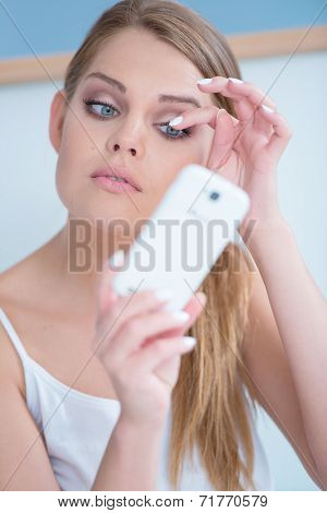 Beautiful girl fixing her eye lashes by using her phone as a mirror