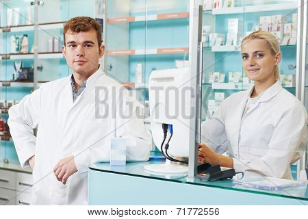 Portrait of two pharmacist chemist workers in pharmacy drugstore