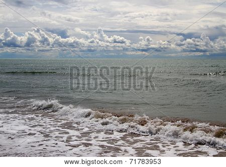 Unspoiled Beach Of The Sea With Clouds