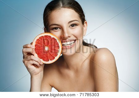 Smiling girl with grapefruit cut in half fruit in hand, with pomelo slice, natural organic raw fresh