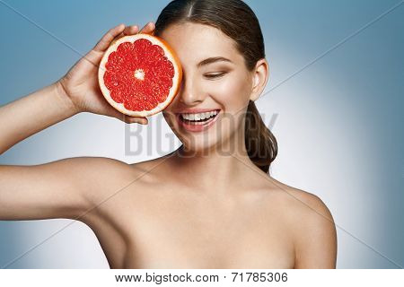 Smiling girl with grapefruit, natural organic raw fresh food concept