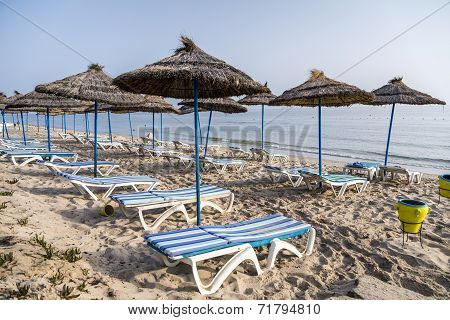 Sun Umbrella On An Empty Beach And Sea Water Horizon. Clear Blue Sky.