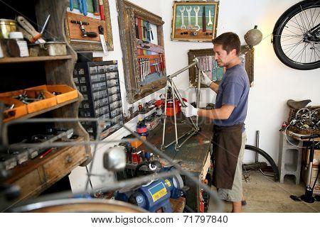 Man in bicycle shop fixing bike frame