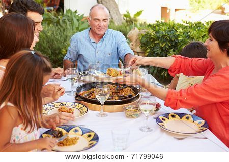 Multi Generation Family Enjoying Meal On Terrace Together