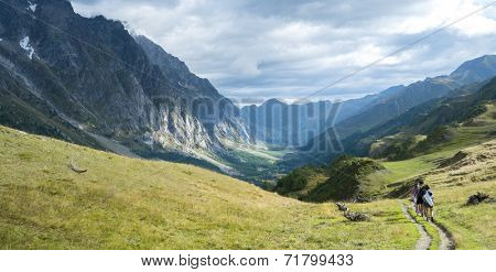 VAL FERRET, ITALY - AUGUST 29: Hikers walking in Val Ferret in Italy, with overcast sky and rocky mountain range. The area is a stage of the Mont Blanc tour. September 29, 2014 in Val Ferret.