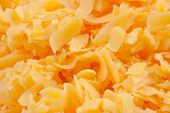stock photo of shredded cheese  - Shredded sharp cheddar cheese in a bowl on a counter top - JPG