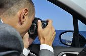 picture of private investigator  - a detective or a paparazzi taking photos from inside a car - JPG