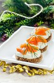 foto of canapes  - canape with salmon and cream cheese with dill for Christmas on a light woody background - JPG