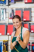 image of air compressor  - Portrait of happy mid adult saleswoman holding air compressor hose in hardware store - JPG
