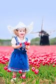 picture of national costume  - Adorable curly toddler girl wearing Dutch traditional national costume dress and hat playing in a field of blooming tulips next to a windmill in Amsterdam region - JPG