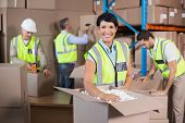 stock photo of vest  - Warehouse workers in yellow vests preparing a shipment in a large warehouse - JPG