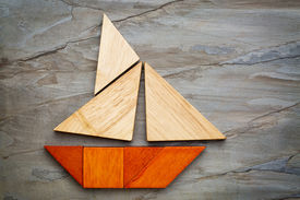 pic of tangram  - abstract picture of a sailing boat built from seven tangram wooden pieces over a slate rock background - JPG