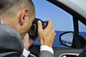 stock photo of incognito  - a detective or a paparazzi taking photos from inside a car - JPG